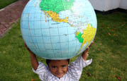 Boy holds up globe outside of an SOS Children's Village in Mexico
