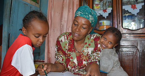 Esetu helps her two grandchildren with their homework