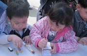 Children decorate recycled milk cartons for Earth Day at SOS Children's Villages Daegu