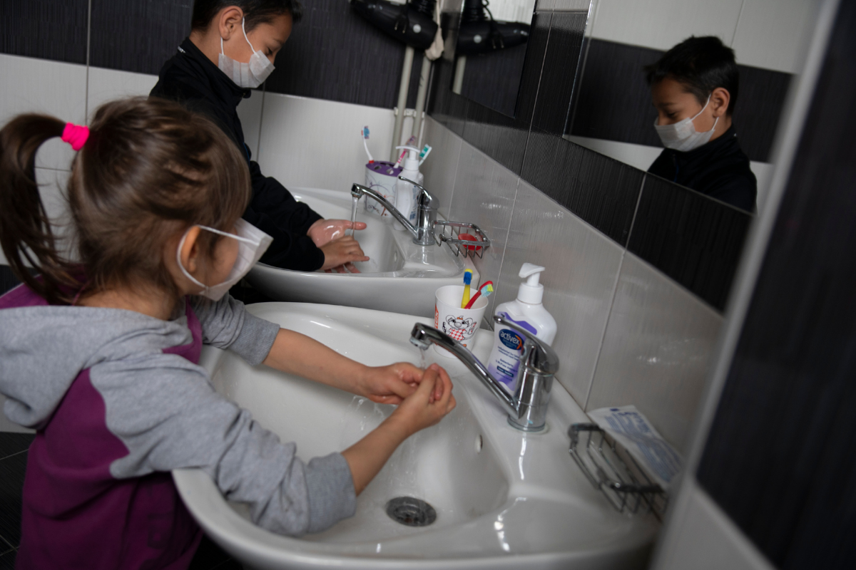 Children washing hands and wearing masks during COVID-19